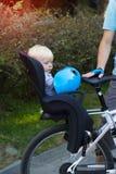 El padre y el hijo que viajan en la bicicleta, niño se está sentando en una bici Foto de archivo