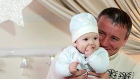 El padre y el hijo, un padre y el bebé juegan en el hogar en el invierno, familia feliz, un buen papá mantiene a un pequeño niño  almacen de metraje de vídeo