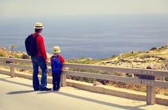 El padre y el hijo viajan con la mochila en el camino imagen de archivo libre de regalías