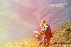 El padre y el hijo viajan en las montañas que miran el mapa Imágenes de archivo libres de regalías