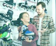El padre y el muchacho sonrientes que se jactan patina sobre ruedas Imagen de archivo