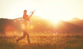El padre y el niño felices de la familia corren en prado con una cometa en summe
