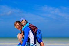 El padre y el pequeño hijo abrazan en la playa del verano Fotos de archivo libres de regalías