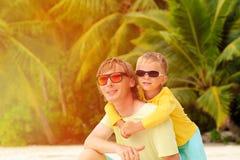 El padre y el pequeño hijo abrazan en la playa del verano Fotografía de archivo libre de regalías