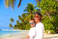 El padre y el pequeño hijo abrazan en la playa del verano Imagenes de archivo