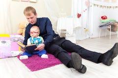 El padre y el pequeño hijo leyeron un libro viejo que se sentaba en la alfombra Fotografía de archivo libre de regalías