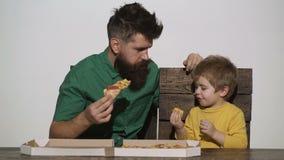 El padre y el hijo almuerzan Pizza para el niño El almuerzo del hombre Un individuo barbudo es un niño pequeño que come en la tab almacen de metraje de vídeo
