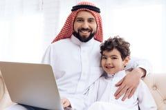 El padre y el hijo barbudos árabes están hojeando las páginas web en el ordenador portátil foto de archivo