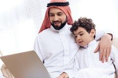 El padre y el hijo barbudos árabes están hojeando las páginas web en el ordenador portátil imagen de archivo