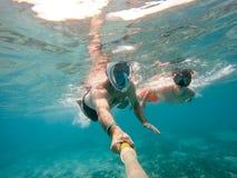 El padre y el hijo bucean en agua poco profunda en los pescados coralinos Imágenes de archivo libres de regalías