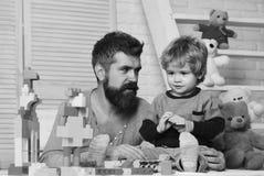 El padre y el hijo con las caras sonrientes crean construcciones coloridas imágenes de archivo libres de regalías