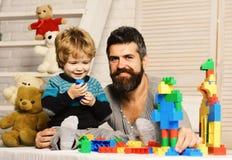 El padre y el hijo con las caras sonrientes crean construcciones coloridas imagen de archivo