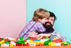 El padre y el hijo crean construcciones Juego barbudo del hombre y del hijo junto Maneras de éxito seguro de enlazar con su hijo  imagen de archivo libre de regalías