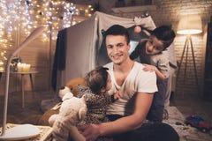 El padre y el hijo están jugando con la pequeña hermana del bebé en la noche en casa Fotos de archivo libres de regalías