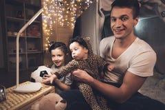 El padre y el hijo están jugando con la pequeña hermana del bebé en la noche en casa Foto de archivo libre de regalías