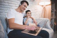 El padre y el hijo están mirando película en el ordenador portátil con palomitas en la noche en casa Foto de archivo libre de regalías