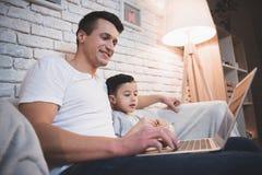 El padre y el hijo están mirando película en el ordenador portátil con palomitas en la noche en casa Foto de archivo