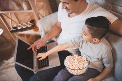 El padre y el hijo están mirando película en el ordenador portátil con palomitas en la noche en casa Fotos de archivo