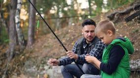 El padre y el hijo están pescando sosteniendo las barras y hablando, el hombre está enseñando al niño pequeño a utilizar el equip almacen de video