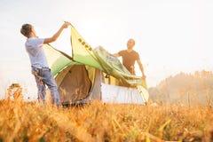 El padre y el hijo instalan la tienda para acampar en el claro soleado del bosque Senderismo con imagen del concepto de los ni?os fotografía de archivo libre de regalías