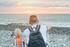El padre y el hijo jovenes se están sentando en la playa del mar Fotos de archivo