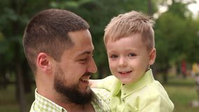 El padre y el hijo juegan en el parque del verano en tiempo soleado caliente Cámara lenta metrajes