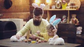 El padre y el hijo pintaron los huevos y el juego de Pascua con el conejito de pascua Familia feliz que se prepara para Pascua Mu metrajes