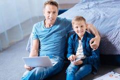 El padre y el hijo que presentan en el dormitorio suelan mientras que estudia Foto de archivo libre de regalías