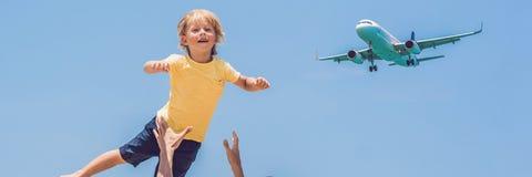 El padre y el hijo se divierten en la playa que miran los aviones de aterrizaje Viajando en un aeroplano con la BANDERA del conce imágenes de archivo libres de regalías