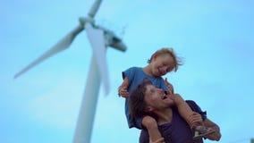 El padre y el hijo se divierten que defiende debajo del generador eléctrico del viento encima de la colina el mar Concepto de la  almacen de video