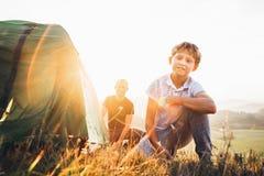 El padre y el hijo se preparan para acampar mountaing, pusieron la tienda Senderismo con imagen del concepto de los niños foto de archivo libre de regalías