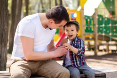 El padre y el hijo se sientan en banco y comen el helado en parque en día soleado de la primavera o de verano Padre e hijo que se imágenes de archivo libres de regalías
