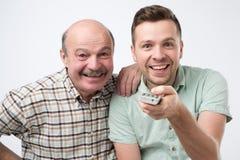 El padre y el hijo seleccionan una película para mirar en la TV fotos de archivo libres de regalías