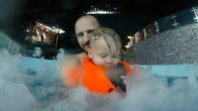 El padre y el hijo tienen un resto en Jacuzzi, cámara lenta, 4k almacen de video