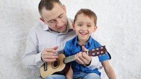 El padre y el hijo tocan la guitarra y cantan El concepto de una familia feliz metrajes