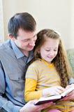 El padre y la hija con el libro Fotos de archivo libres de regalías