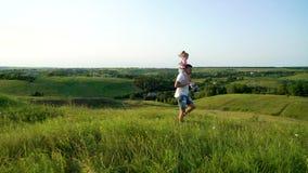 El padre y la hija en cuello comparten amor que caminan juntos en alto campo de hierba metrajes
