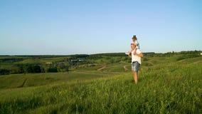 El padre y la hija en cuello comparten amor que caminan juntos en alto campo de hierba almacen de video