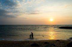 El padre y la hija en el sol de la playa fijaron 2 Imagenes de archivo