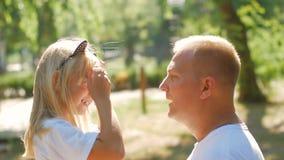 El padre y la hija felices son torcidos y de risas en la luz del sol En el parque metrajes