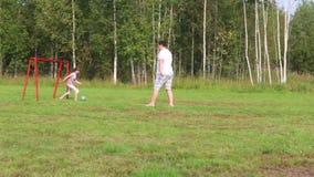 El padre y la hija juegan con la bola en campo verde con la puerta del fútbol en el verano almacen de metraje de vídeo