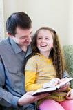 El padre y la hija leyeron el libro Imagen de archivo libre de regalías