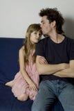 El padre y la hija se está sentando en el sofá Fotografía de archivo libre de regalías