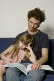 El padre y la hija se están sentando Imagen de archivo libre de regalías