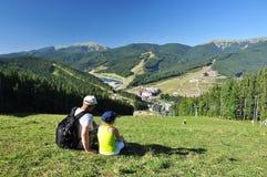 El padre y la hija se sientan en la hierba y admiran el paisaje de la montaña imágenes de archivo libres de regalías