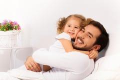 El padre y la hija sonrientes abrazan en la cama blanca Imágenes de archivo libres de regalías