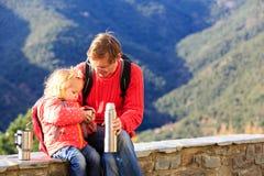 El padre y la hija viajan en montañas que beben té caliente Fotografía de archivo libre de regalías