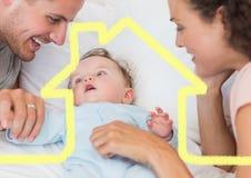 El padre y la madre con el bebé sobrepuesto con la casa forman imágenes de archivo libres de regalías
