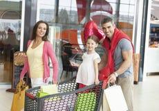 El padre y la madre empujan a la hija joven en carretilla de las compras a través de alameda Imagen de archivo