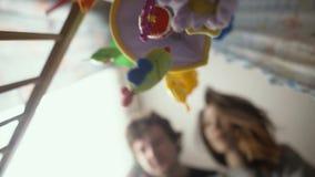 El padre y la madre felices juegan con el bebé en punto de vista del niño del pesebre metrajes